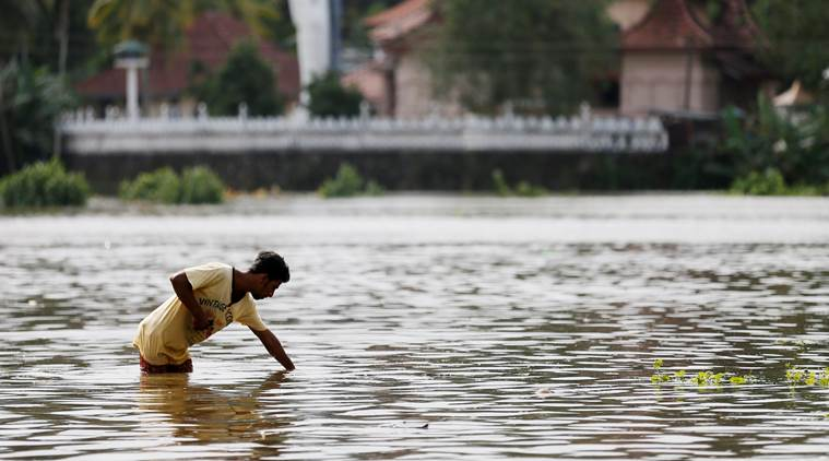 A man searches the water on a flooded road in Dodangoda village in Kalutara